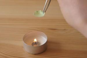 Sciogliendo la stoffa con sulla candela con le pinzette per creare un piccolo petalo